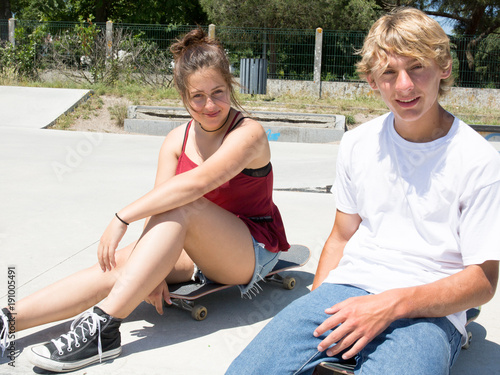 teenager boy and girl in skatepark with skateboard