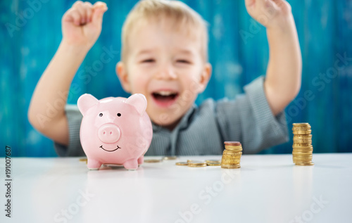 two years old child sitting on the floor and putting a coin into a piggybank