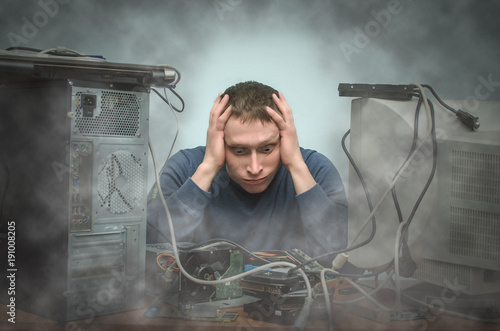 tired and bored computer repairman is sitting on his workplace in