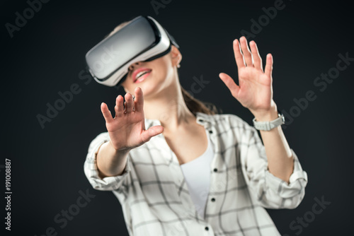 woman gesturing and using virtual reality headset, isolated on black