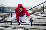 Young fitness man runner stretching legs before running on the stairs