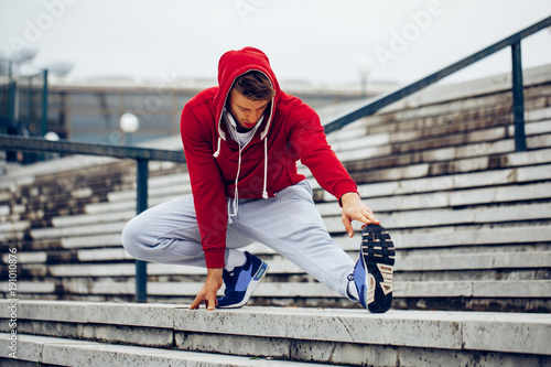 Fotobehang Hardlopen Young fitness man runner stretching legs before running on the stairs