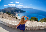 Beautiful young woman tourist looking at Myrtos Beach in Cephalonia Island Greece from above