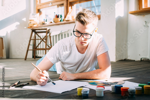 Young man artist paints a picture