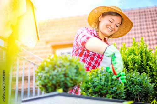 Sticker Fröhliche Frau im Garten beim Pflanzenpflege