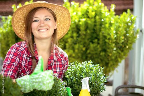 Fröhliche Frau im Garten beim Pflanzenpflege