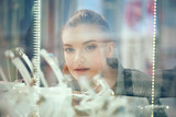 Close up shot of attractive young woman out shopping for jewelry. Girl lookin at jewellery in a display cabinet.
