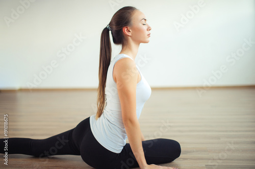 Keuken foto achterwand School de yoga woman practicing yoga pose at yoga healthy sport gym, girl stretching her legs