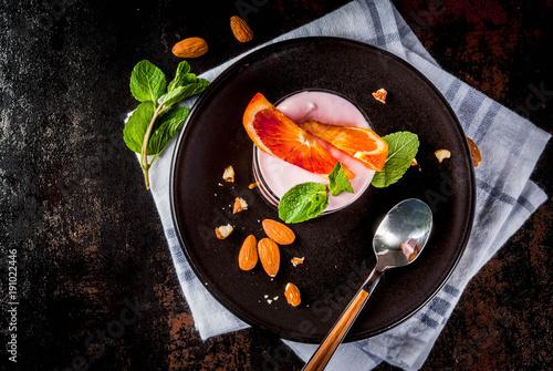 Healthy breakfast, Blood Orange Parfait with granola. yogurt, almond and mint, dark rusty background, copy space top viewkfast, Blood Orange Parfait