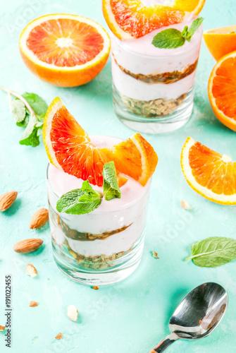 Healthy breakfast, Blood Orange Parfait with granola. yogurt, almond and mint, light blue background, copy space