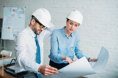 serious architects discussing building plan at office