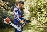 Man with weedwacker cutting the grass - 191025656