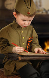 The little boy in the old-fashioned Soviet military uniform writes a letter - 191029258