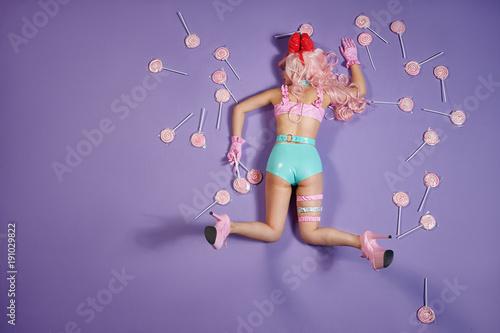 eine cosplay verkleidete Dame in mintfarbenen hotpants liegt auf einem lila Untergrund auf dem Bauch, als wäre sie aus dem Fenster gefallen. um sie herum liegen eine menge großer Lollys