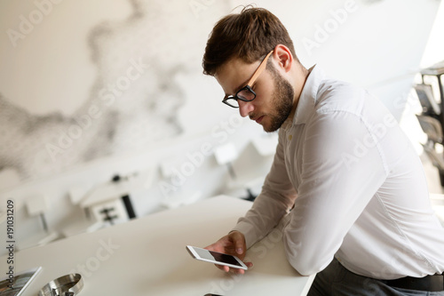 Handsome businessman using phone and wearing glasses