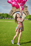 Girl near the Eiffel tower in Paris with huge bunch of pink balloons - 191032672