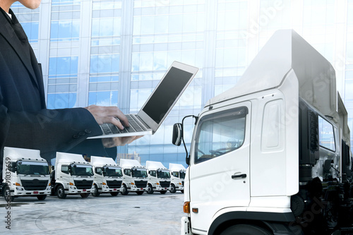 Business man is working with laptop and control trucking as in logistics concept.