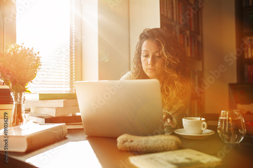 Young female curly hair student study at home.She using laptop and learning online.