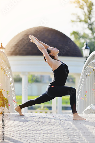 Fotobehang School de yoga A woman yogi makes asanas on the bridge in the summer in a park.