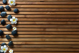 black massage pebbles and spa flowers set on wooden board - 191036817