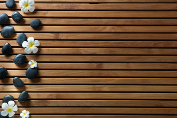 black massage pebbles and spa flowers set on wooden board © STUDIO GRAND WEB