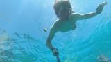 Young man snorkeling between corals in bright blue ocean - 191037267