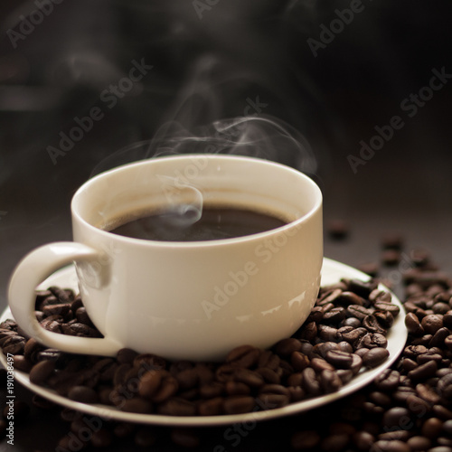 Poster Koffiebonen Hot cup of coffee with smoke on black background