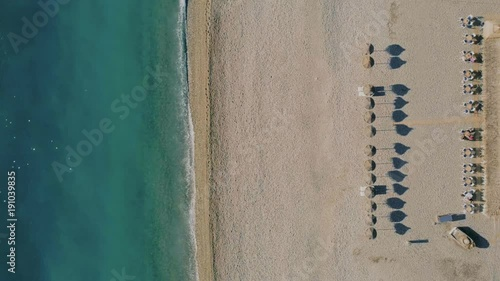 Aerial drone flyover cinemagraph of symmetrical beach front line with cabanas and umbrellas lined up, minimalistic resort view, calm paradise like maldives travel destination, waves and ocean © marioav