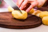 Female hands cut potatoes on wooden board - 191040844
