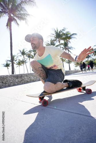 Fotobehang Skateboard Trendy guy riding skateboard in Miami South Beach