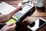 Payment by card in cafe with terminal and keyboard on wooden bac - 191044601