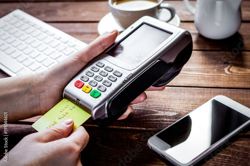 Payment by card in cafe with terminal and keyboard on wooden bac