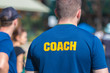 back of a coach's blue color shirt with the word Coach in yellow color written on
