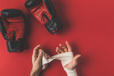cropped shot of boxer covering up hands in elastic bandage before fight on red surface
