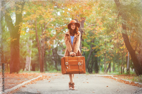 Young redhead woman with suitcase