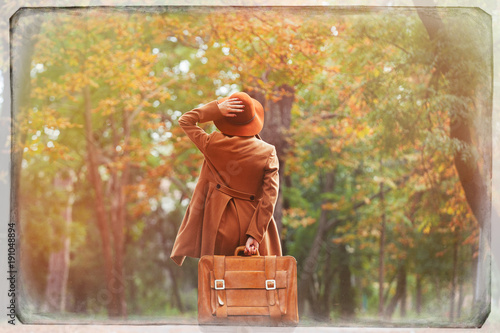 Back side view at woman with suitcase