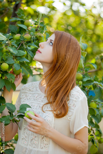 Young redhead girl in apple tree garden