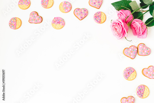 Gingerbread cookies and roses on white background. Flat lay. top view.