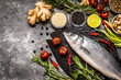 Fish, sea bass and ingredients for cooking: vegetables, spices, herbs
