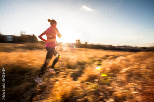 Young woman running outdoors on a lovely sunny winter/fall day (motion blurred image) - 191056459