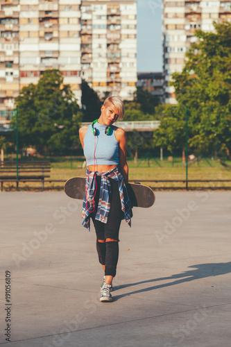 Fotobehang Skateboard Young woman posing with skateboard in skate park