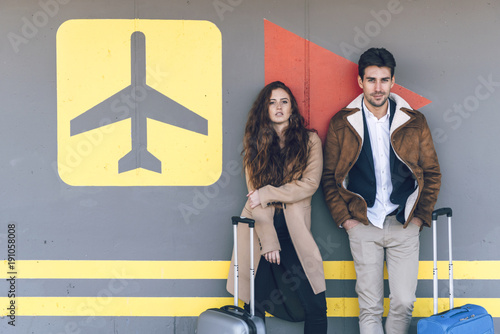 Young couple with suitcases standing at wall in airport and looking at camera.