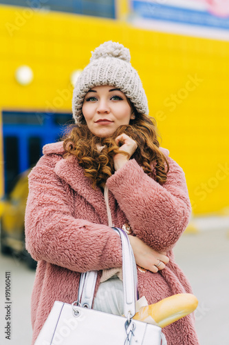 Young smiling woman standing on supermarket parking lot and holding bag with baguette