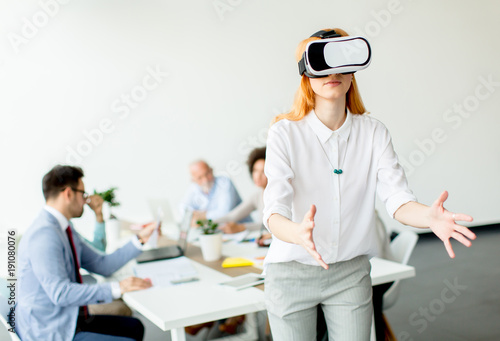 Foto Murales Young woman using virtual reality simulator in the office
