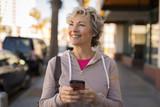 Mature caucasian woman walking texting cell phone - 191085476
