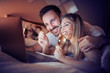 Couple watching movie in bed