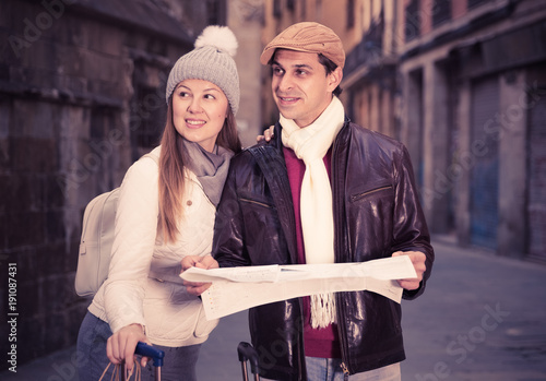 Cheerful man and woman with map