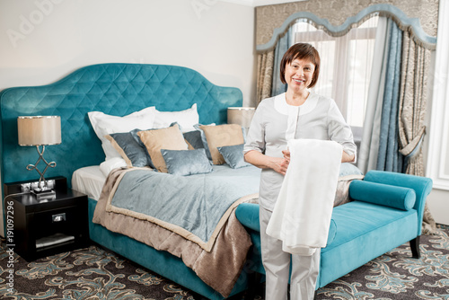 Portrait of a senior chambermaid in uniform standing with towel in the luxury hotel bedroom