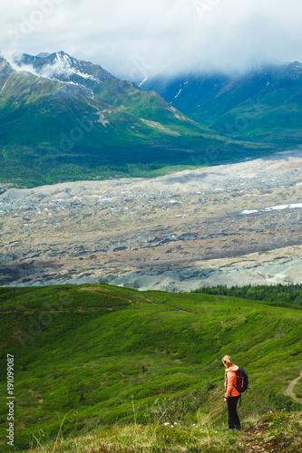 Woman hiking in the mountains. Enjoying the view. Active life. Alaska range. Glacier.