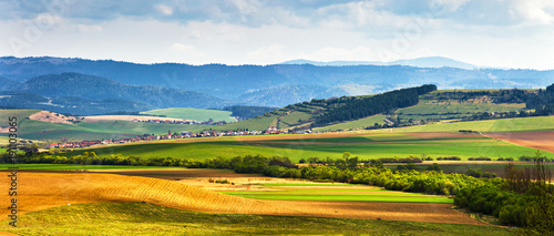 Papiers peints Photos panoramiques Spring green field and meadows on the hills
